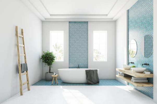 White and blue bathroom interior with a round white tub, two narrow windows, a tree in a pot and a ladder in a corner